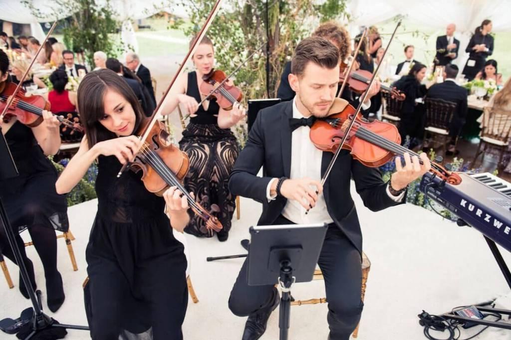 Orquestra tocando ao ar livre, com violinos em primeiro plano